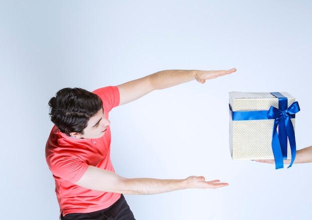 Man ontvangt en houdt een witte geschenkdoos omwikkeld met blauw lint met beide handen