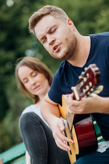 Man op bank gitaar spelen en zingen