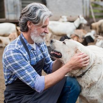 Man op boerderij spelen met hond