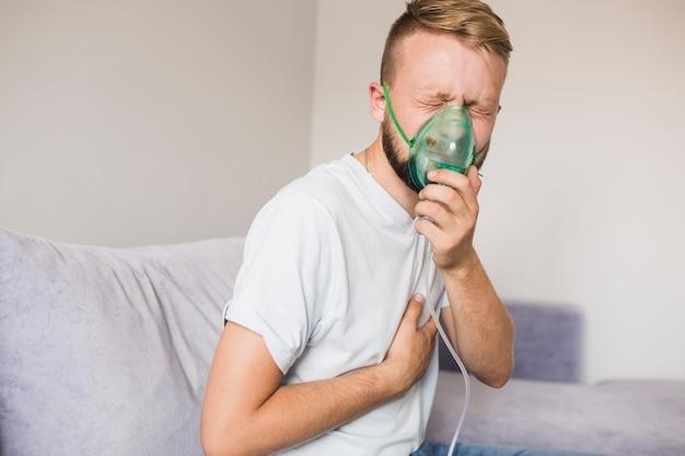 Man op de bank met behulp van astma vernevelaar