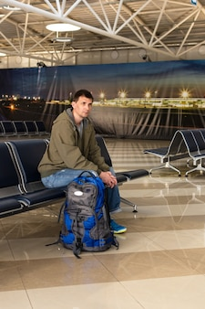 Man op de luchthaven met bagage wachtend op het instappen in zijn vliegtuig, de passagier zit op de stoelen op de luchthaven