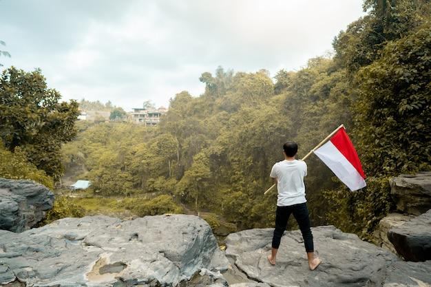Man op de top van de heuvel in de ochtend stijgende indonesische vlag viert onafhankelijkheidsdag