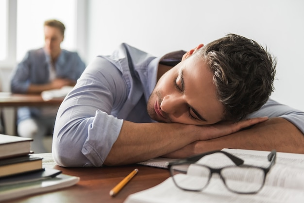 Man op de voorgrond dut op het bureau