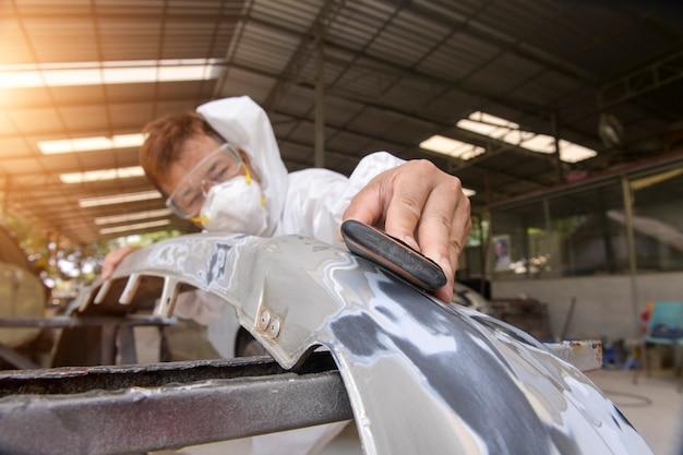 Man op een auto wassen autowassen met een polijstmachine. auto detaillering - handen met orbitale polijstmachine in auto reparatiewerkplaats. selectieve aandacht.