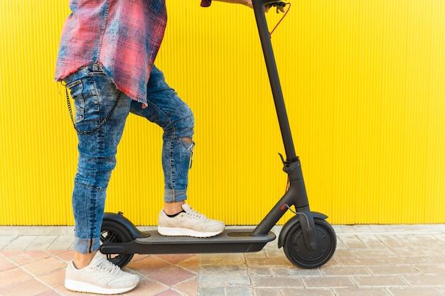 Man op een elektrische scooter op gele achtergrond.