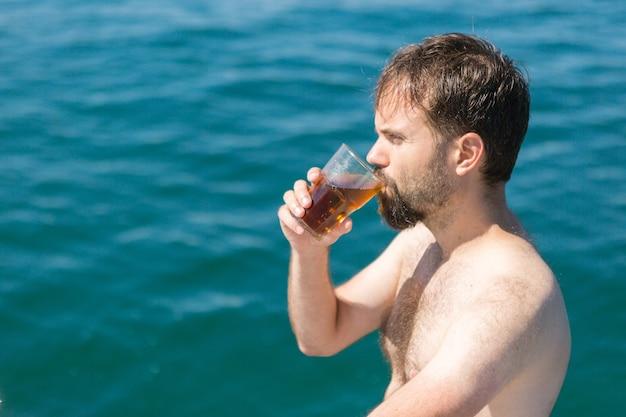 Man op een jacht in de zomer, hand met een glas rum met cola
