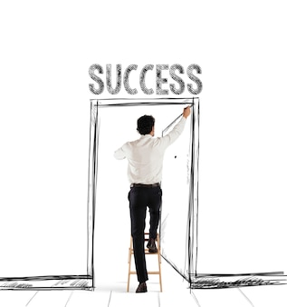 Man op een ladder tekent met een pen een deur met geschreven succes