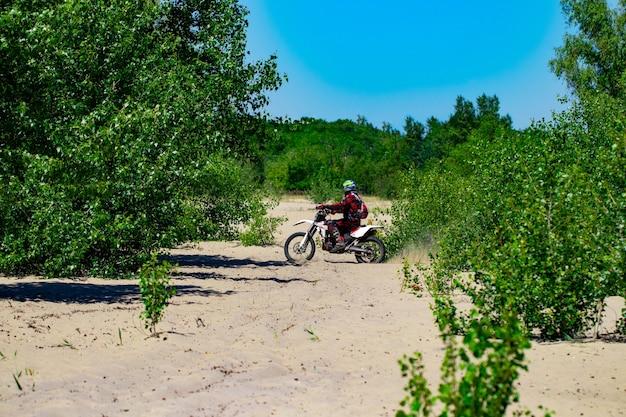 Man op een motorfiets op het strand.