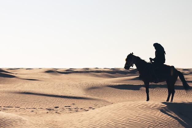 Man op een paard in de woestijn.