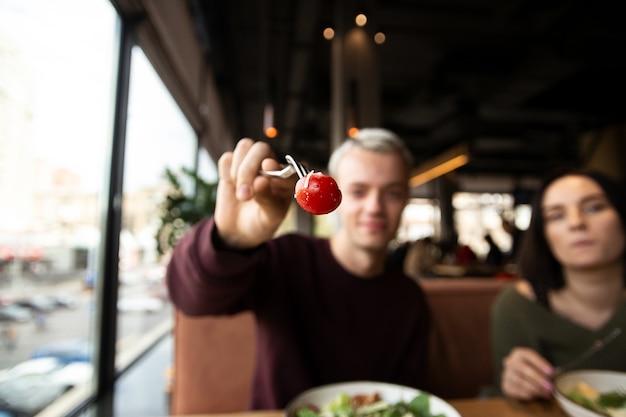 Man op een restaurant met een tomaat