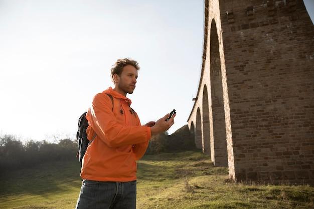 Man op een road trip poseren voor aquaduct terwijl hij kompas vasthoudt