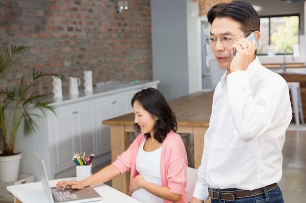 Man op een telefoongesprek terwijl zwangere vrouw laptop gebruikt