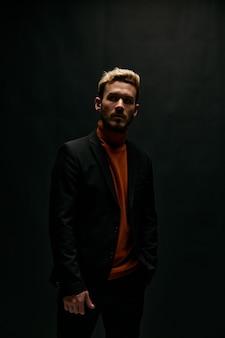 Man op een zwarte achtergrond in een oranje trui en leren jas