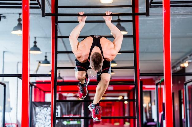 Man op freestyle calisthenics training in de sportschool