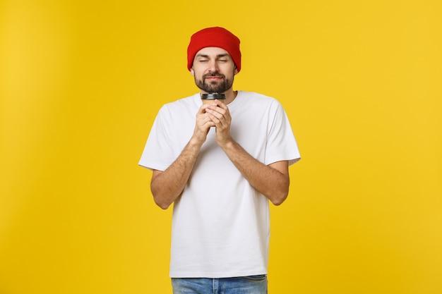 Man op geïsoleerde levendige gele kleur die een kopje koffie neemt in een papieren afhaalbeker en glimlacht omdat hij de dag goed zal beginnen