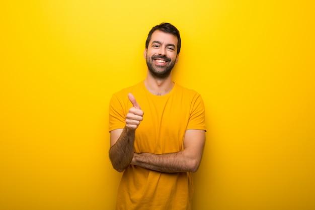 Man op geïsoleerde levendige gele kleur geven een duim omhoog gebaar omdat er iets goeds is gebeurd