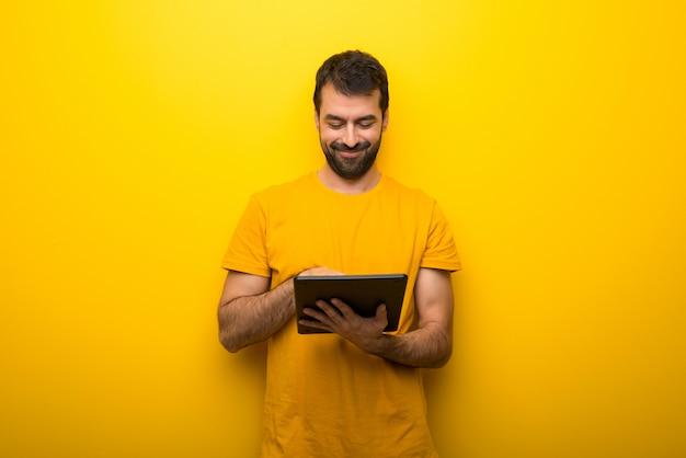Man op geïsoleerde levendige gele kleur met een tablet