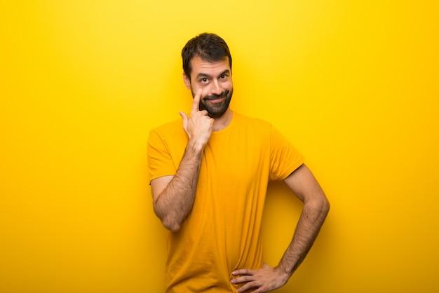 Man op geïsoleerde levendige gele kleur op zoek naar de voorkant