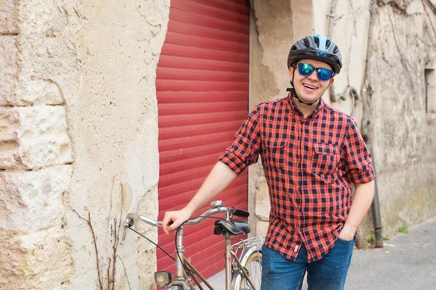 Man op helm, rood shirt en zonnebril houden fiets buiten