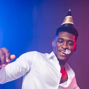 Man op het feest blaast in een feesthoorn