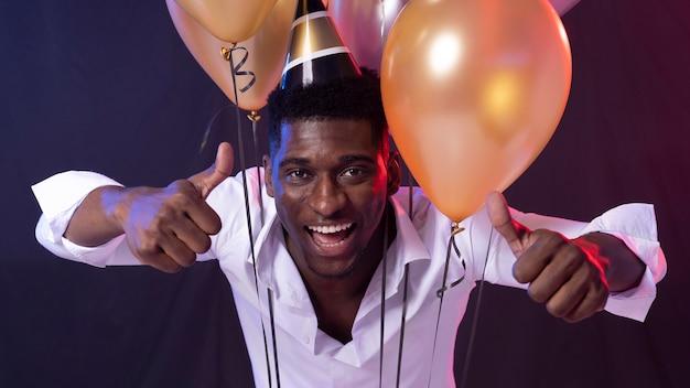 Man op het feest met papieren kegel hoed en ballonnen