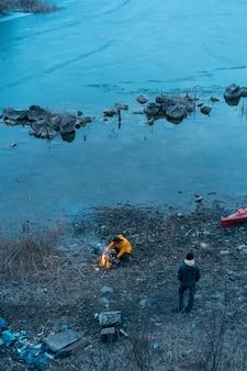 Man op het meer maakt een vuur