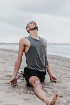 Man op het strand doet de split in yogaroutine