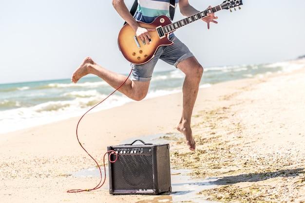 Man op het strand met muziekinstrumenten