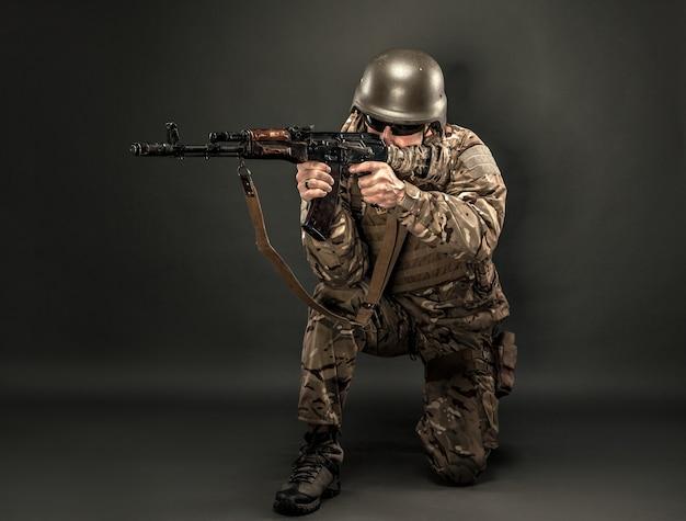 Man op knie gericht met geweer.