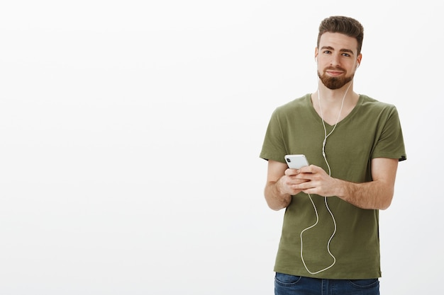 Man op lied brengt mooie herinneringen. portret van charmante schattige en zachte bebaarde vriend in olijf t-shirt glimlachend opgetogen met ontspannen grijns als luisteren muziek in oortelefoons, smartphone houden
