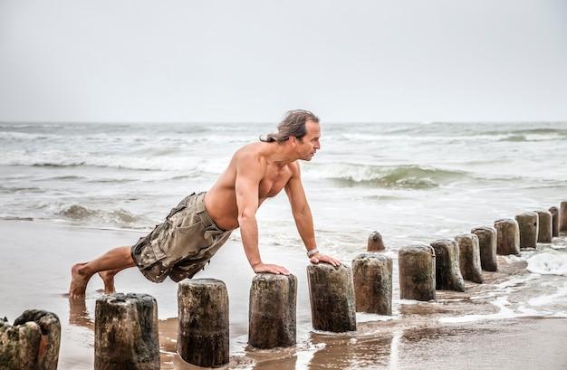 Man op middelbare leeftijd doet pushups op het strand
