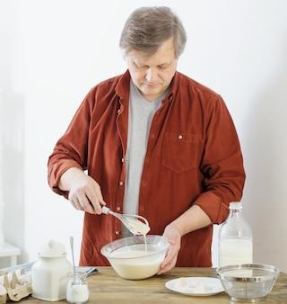 Man op middelbare leeftijd pannenkoekdeeg kneden op witte keuken