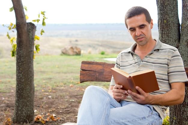 Man op middelbare leeftijd zittend ontspannen op een houten bankje genieten van een boek in de tuin