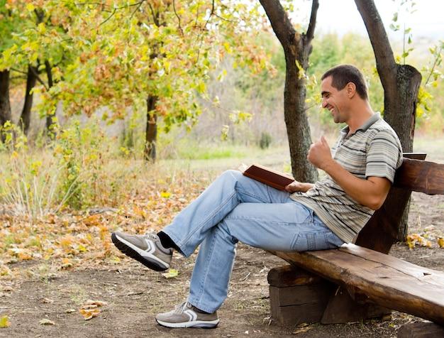 Man op middelbare leeftijd zittend op een rustieke houten bank op het platteland, lachend en lezend, genietend van zijn boek