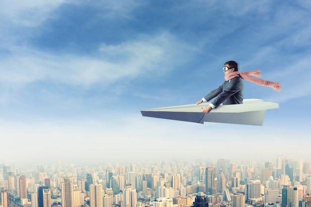 Man op papieren vliegtuigje boven de stad