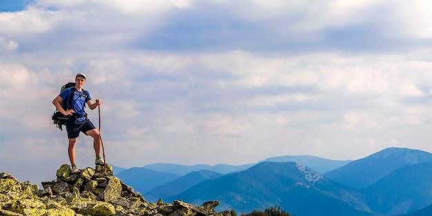 Man op piek van berg. emotionele scène. jonge mens met rugzak die zich met opgeheven handen bovenop een berg bevindt en van bergmening geniet. wandelaar op de bergtop. sport en actief leven concept.