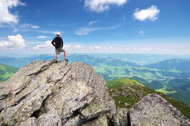 Man op piek van berg.
