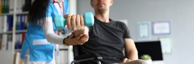 Man op rolstoel houdt halter in zijn handen. arts en jonge man in rolstoel. behandeling en herstel verloren functies. revalidatie na blessures. herstel motorische functies hand