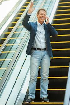 Man op roltrap. volledige lengte van zelfverzekerde volwassen man die op de mobiele telefoon praat en naar iemand zwaait terwijl hij met de roltrap naar beneden gaat
