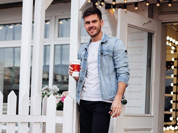 Man op straat koffie drinken in een spijkerjasje