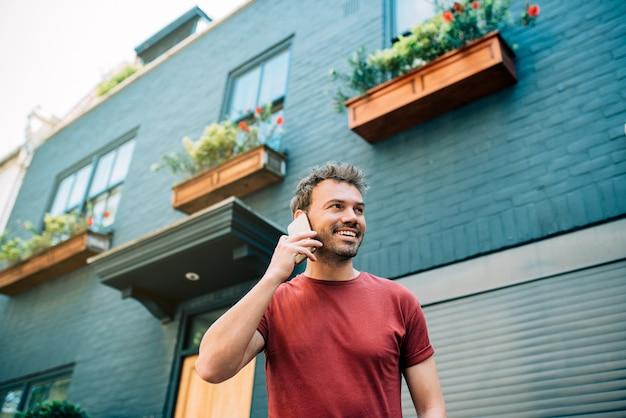 Man op straat met behulp van de mobiele telefoon