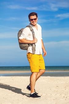 Man op strand glimlachend en gelukkig hipster heldere outfit dragen. jong mannelijk model dat van de zomervakantie geniet door de oceaan met modieuze rugzak