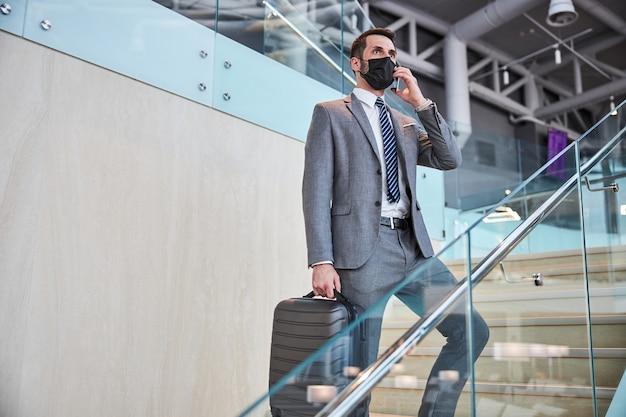 Man op trap die op een mobiele telefoon spreekt