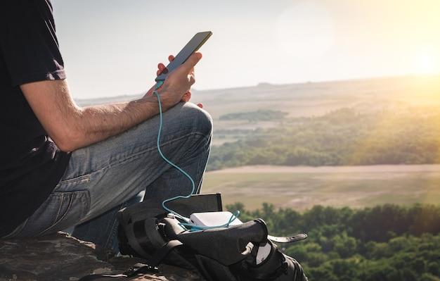 Man op wandeling gebruikt smartphone tijdens het opladen vanaf de powerbank op de rots bij zonsopgang