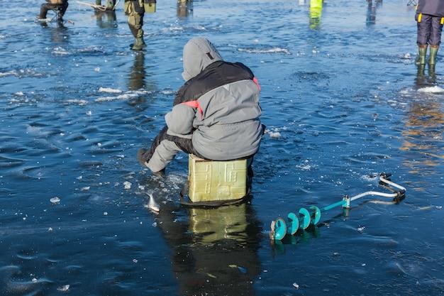 Man op wintervissen, mensen op het ijs van het bevroren meer, vissers, stadslandschap,