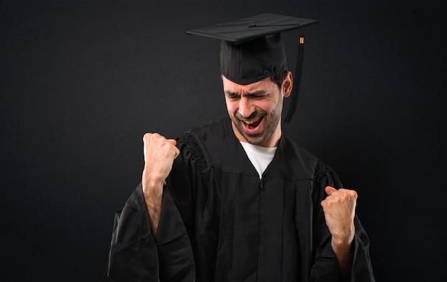 Man op zijn afstudeerdag university viert een overwinning en is blij dat hij een prijs heeft gewonnen