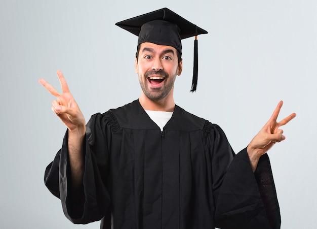 Man op zijn afstuderen dag universiteit glimlachend en overwinning teken met beide handen tonen