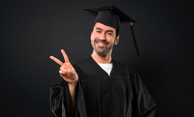 Man op zijn afstuderen dag universiteit glimlachend en overwinning teken met een vrolijk gezicht tonen
