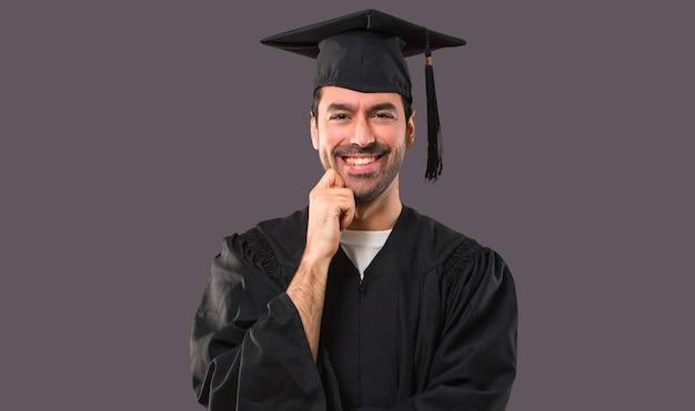 Man op zijn afstuderen dag universiteit lacht met een zoete uitdrukking op violette achtergrond