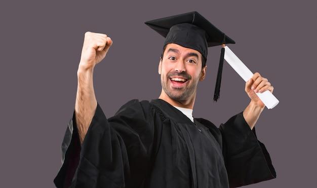 Man op zijn afstuderen dag universiteit viert een overwinning en verrast om succesvol te zijn
